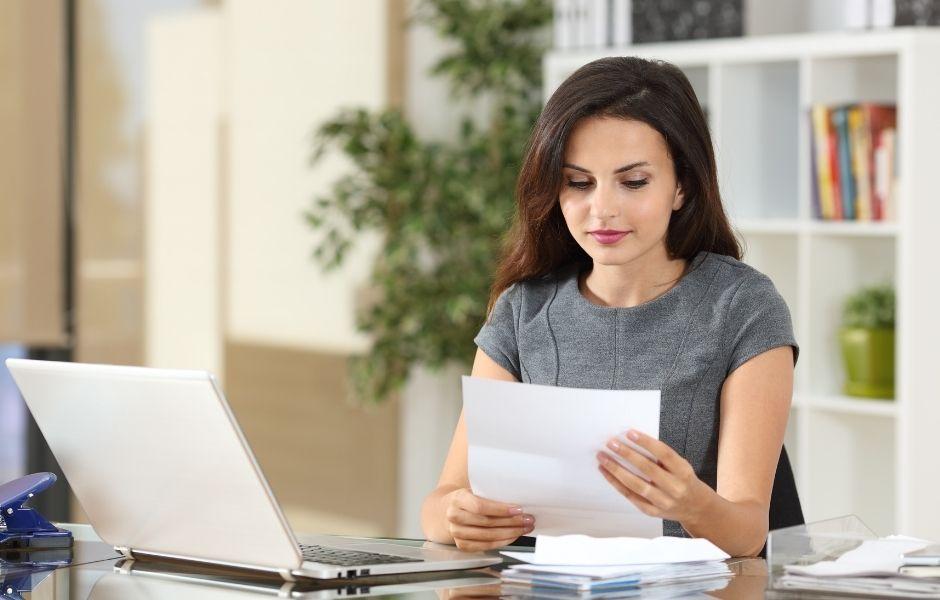 female reading a letter at her desk