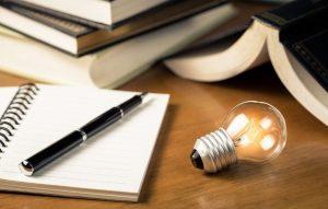 content creation process concept - open notepad next to a lit lightbulb