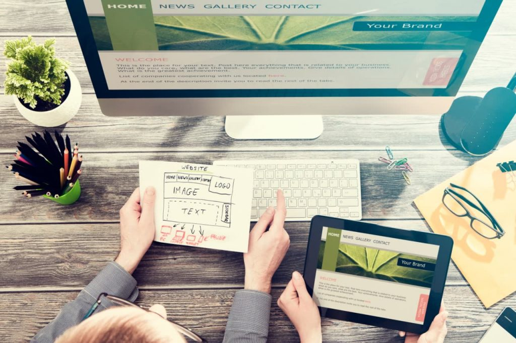 responsive and accessible web design. People planning website design with paper mockup and digital representation