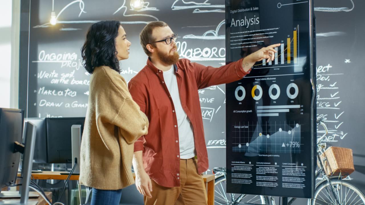 man and woman looking at an analysis graph