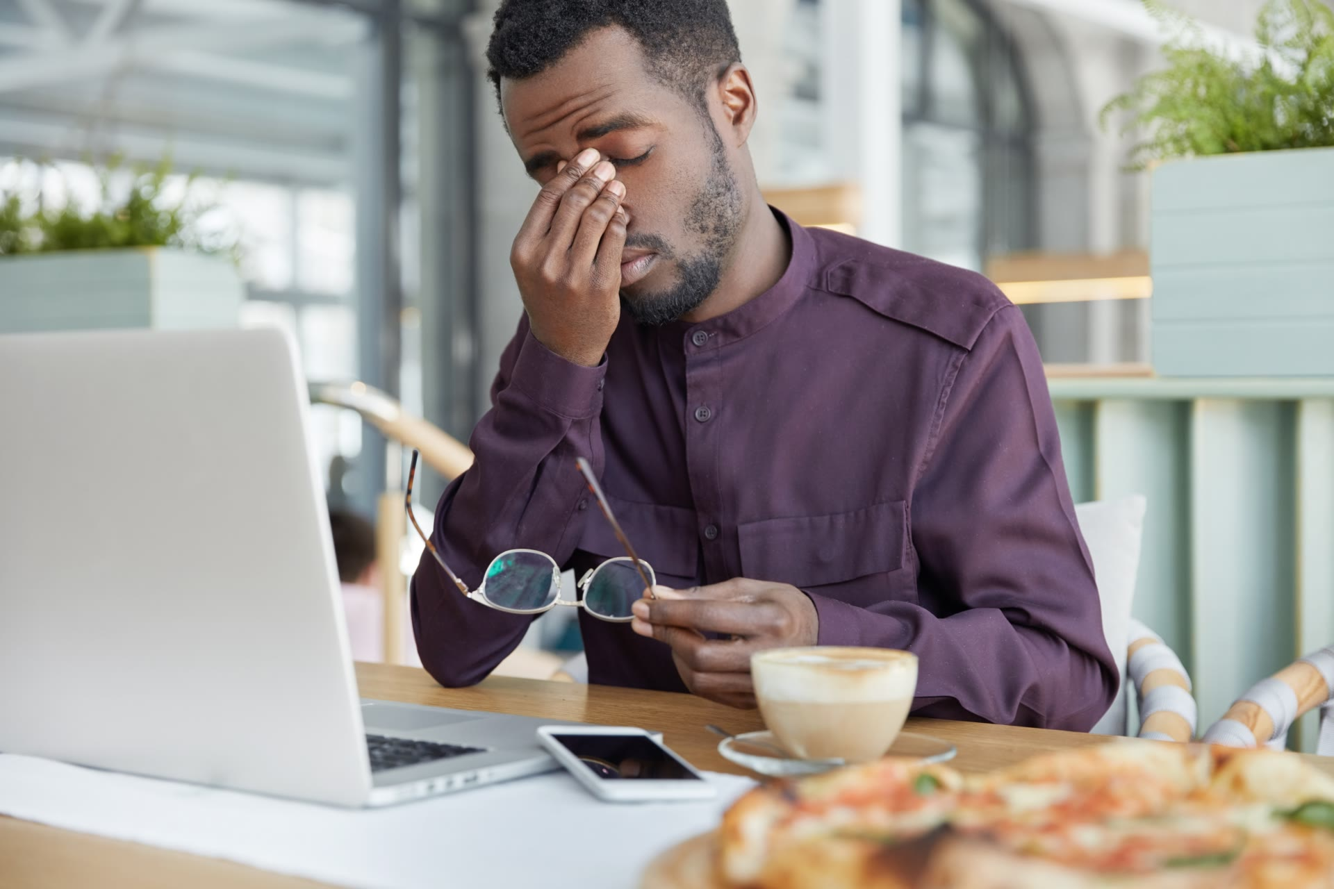 frustrated man at the computer rubbing his eyes